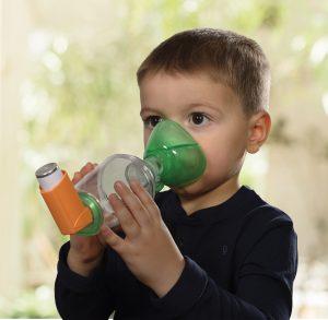 Enfant avec une chambre d'inhalation pédiatrique TipsHaler avec masque cloisonné OrHal